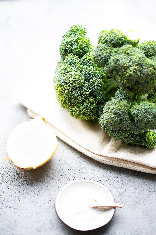 Bonche de brocoli junto a media cebolla y sal