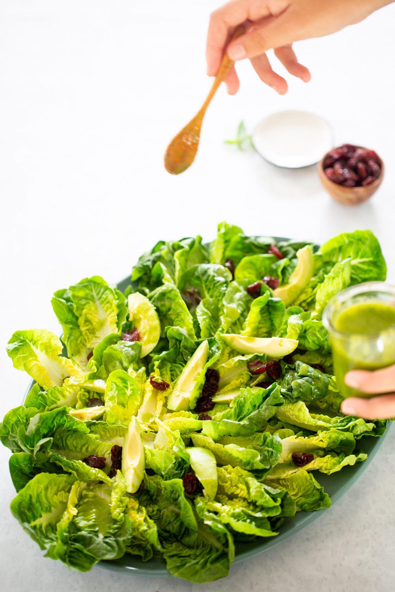 gotas de Aderezo de albahaca cayendo sobre ensalada de hojas verdes