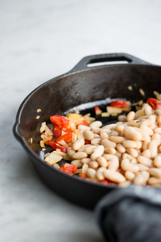 onion, red bell pepper and navy beans in pan