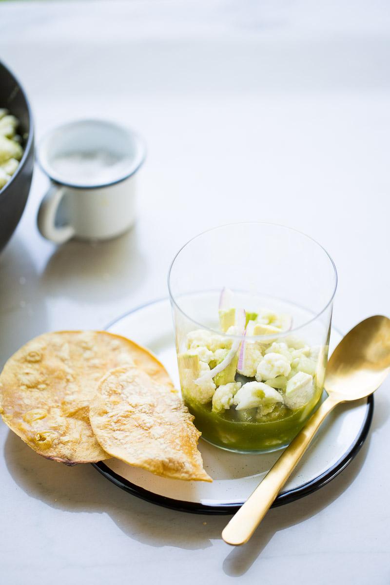 Aguachile de coliflor servido en un vaso y tostadas de maíz aun lado.