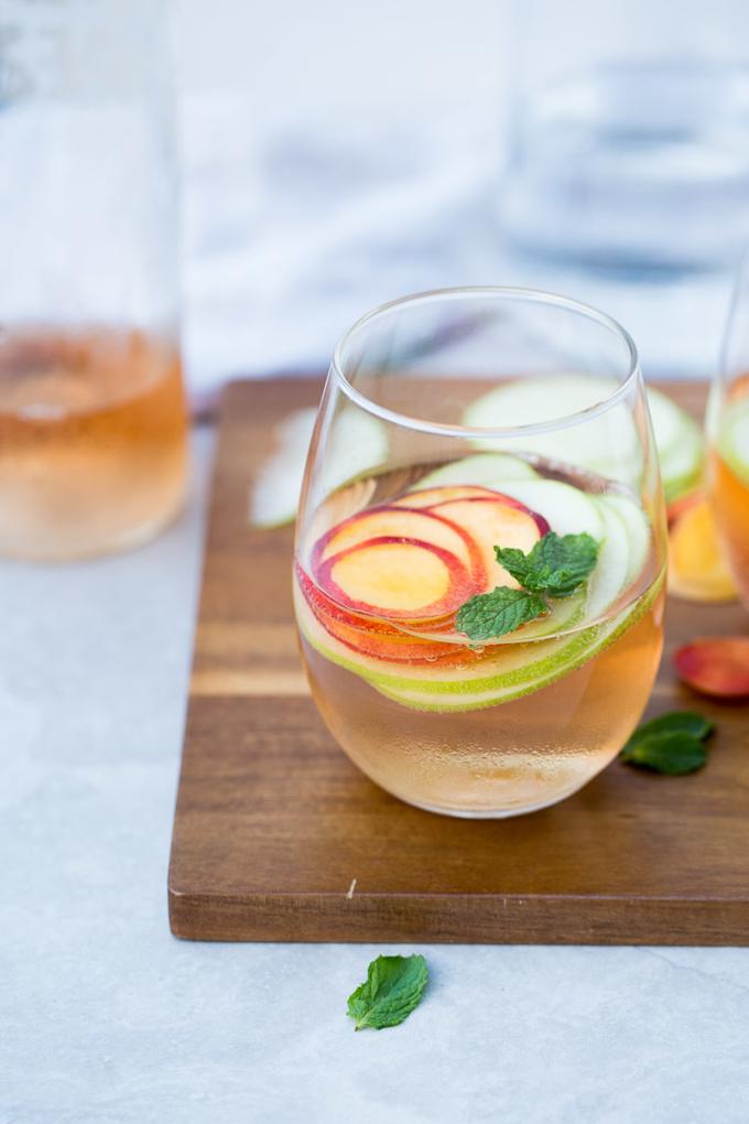 Receta para hacer sangría de verano con vino rosado y fruta de la estación.