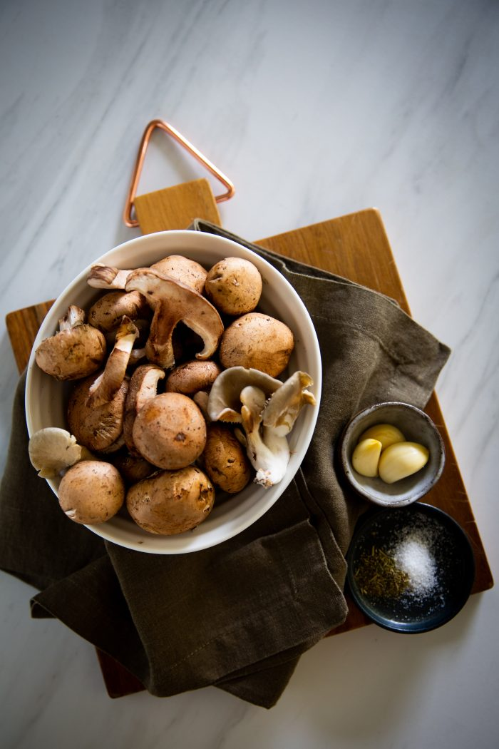 Diferentes tipos de champiñón en un tazón, ajo y sal en platos a un lado.